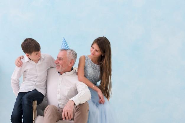 Grootvader en kleinkinderen die op wapenstoel zitten op blauwe achtergrond Gratis Foto