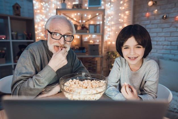 Grootvader en kleinzoon kijken film op laptop Premium Foto