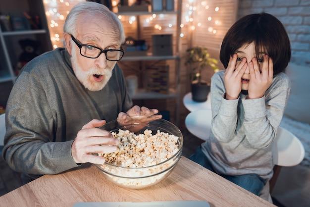 Grootvader en kleinzoon kijken naar enge film Premium Foto