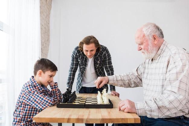 Grootvader en kleinzoon spelen schaak Gratis Foto