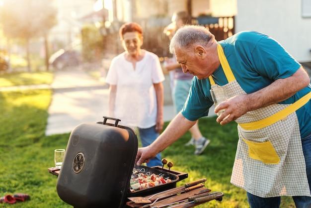 Grootvader met schort die bij de grill controleren en glas bier houden terwijl status in de binnenplaats. Premium Foto