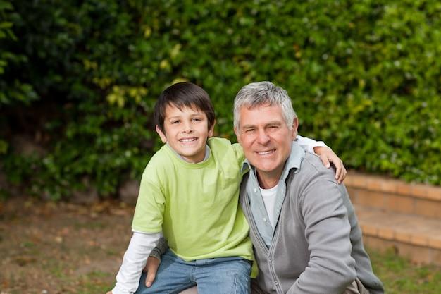 Grootvader met zijn kleinzoon kijken naar de camera in de tuin Premium Foto