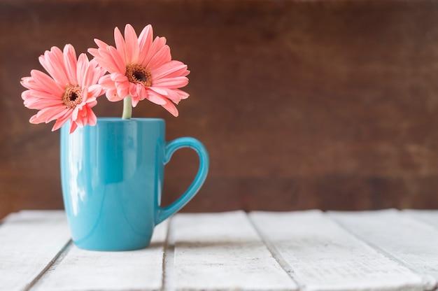 Grote achtergrond met decoratieve blauwe mok en bloemen Gratis Foto