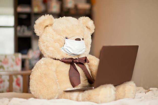 Grote bruine beer speelgoed in medische masker zittend op het bed met digitale tablet-laptop notebook. bel vrienden of ouders online. Premium Foto