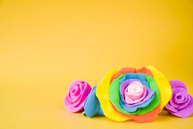 Grote creatieve mooie roos gemaakt met klei op gele achtergrond Gratis Foto