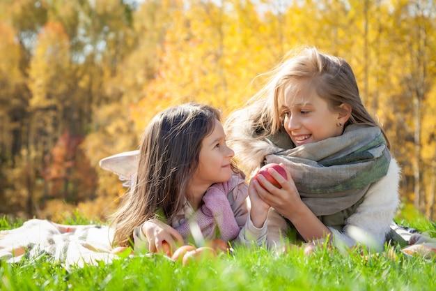 Grote en kleine zusjes liggen op de plaid, spelen met rode appels op de achtergrond van groen gras van gouden bomen van de herfstbos Premium Foto