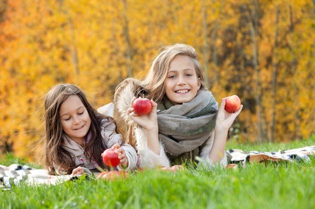 Grote en kleine zusjes liggen, spelen met rode appels op de achtergrond van groen gras van gouden bomen van de herfstbos Premium Foto