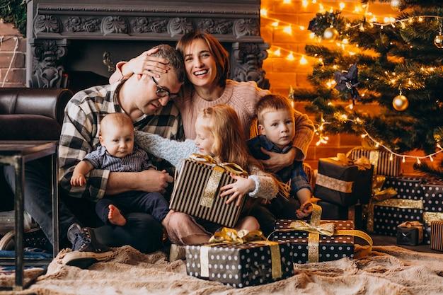 Grote familie op kerstavond met cadeautjes per kerstboom Gratis Foto
