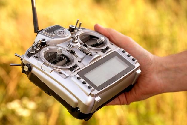Grote grijze afstandsbediening met veel hendels en knoppen om de drone te besturen. in de hand van een man. selectieve aandacht, close-up. Premium Foto