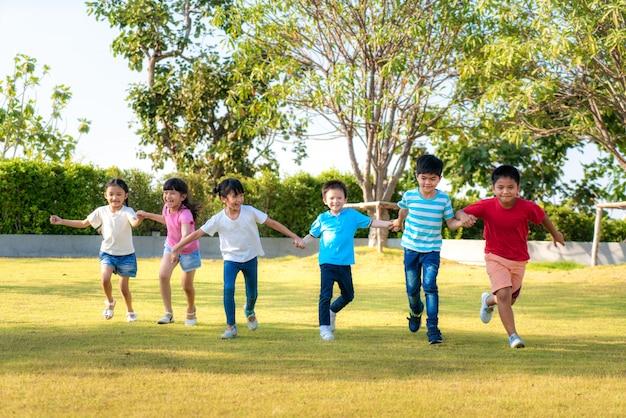 Grote groep gelukkige aziatische glimlachende vrienden die van kleuterschooljonge geitjes handen houden die en in het park op zonnige de zomerdag in vrijetijdskleding spelen lopen. Premium Foto