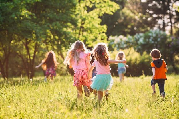 Grote groep kinderen, vrienden jongens en meisjes die in het park op zonnige zomerdag in vrijetijdskleding lopen. Premium Foto