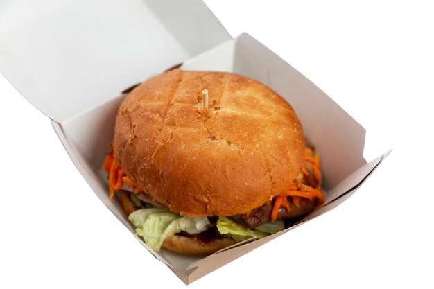 Grote hamburger om van te watertanden in een kartonnen doos. junkfood en fastfood. geïsoleerd op witte achtergrond. Premium Foto