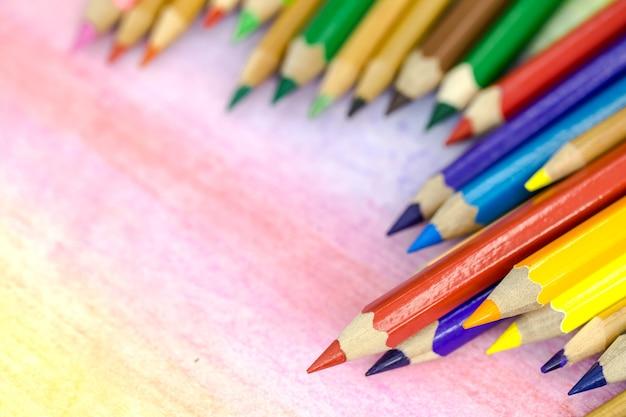 Grote kleurpotloden close-up op een gekleurde achtergrond met kleurpotloden Gratis Foto