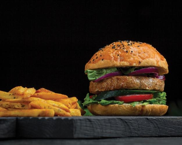 Grote mac-hamburger en aardappels stokken op een donkere houten bord. Gratis Foto