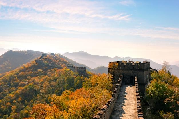 Grote muur van china in kleurrijke herfst seizoen tijdens zonsondergang in de buurt van beijing, china. Premium Foto