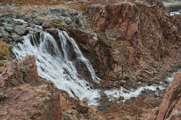 Grote natuurlijke stapstenen over een stromende beek, rivier, meer, kanaal, vredig, nog steeds sereen, ontspannend, buitenwandeling, wandeling, verkenning, reizen Premium Foto