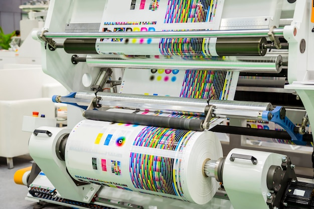 Grote offsetdrukpers met een lange rol papier in de productielijn van een industriële printermachine. Premium Foto