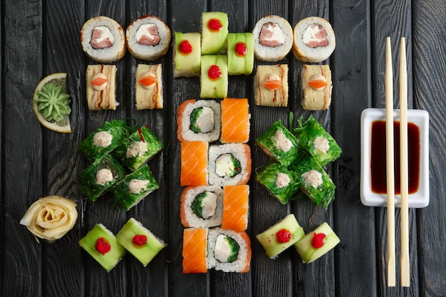 Grote reeks broodjes, sojasaus en eetstokjes (hashi) op dark Premium Foto