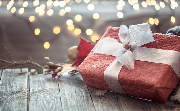 Grote rode aanwezig over kerstverlichting bokeh in huis op houten tafel met trui op een achtergrond en decoraties. winterstemming, vakantiedecoratie, magische kerst. Gratis Foto