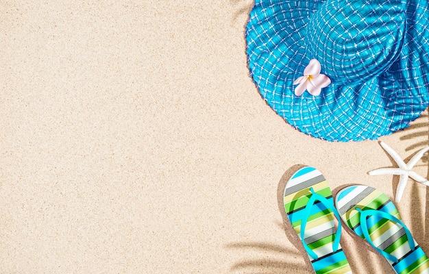 Grote ronde blauwe zomerhoed en kleurrijke gestreepte sandalen op zand met palmboomschaduw, tp-weergave, kopie ruimte Premium Foto
