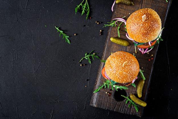 Grote sandwich - hamburger hamburger met rundvlees, tomaat, basilicum kaas en rucola. bovenaanzicht. plat leggen Premium Foto
