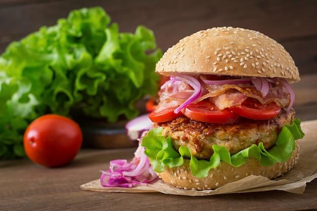 Grote sandwich - hamburgerburger met rundvlees, rode ui, tomaat en gebakken spek. Premium Foto