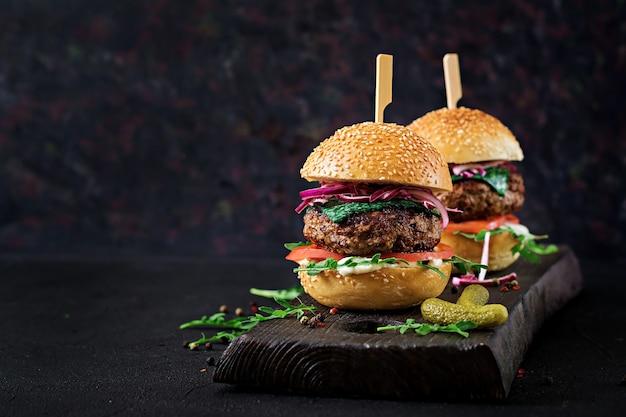 Grote sandwich - hamburgerburger met rundvlees, tomaat, basilicumkaas en rucola. Premium Foto
