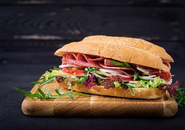 Grote sandwich met ham, salami, tomaat, komkommer en kruiden Premium Foto