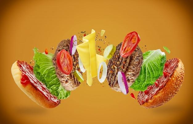 Grote smakelijke zelfgemaakte hamburger met vliegende ingrediënten op een bruine achtergrond. het concept van voedsel levitatie Premium Foto