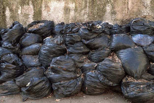 Grote stapel afval of bladeren in zwarte plastic zakken ligt buiten op een asfaltoppervlak. het concept van vervuilingsomgeving. Premium Foto