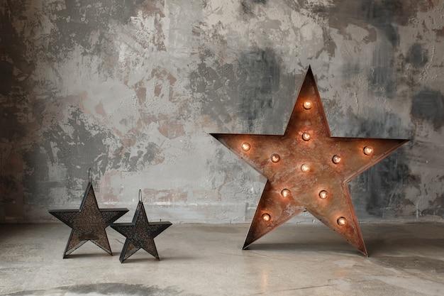 Grote ster met bollichten en kleine op concrete muurachtergrond, zolder binnenlands decor. Gratis Foto