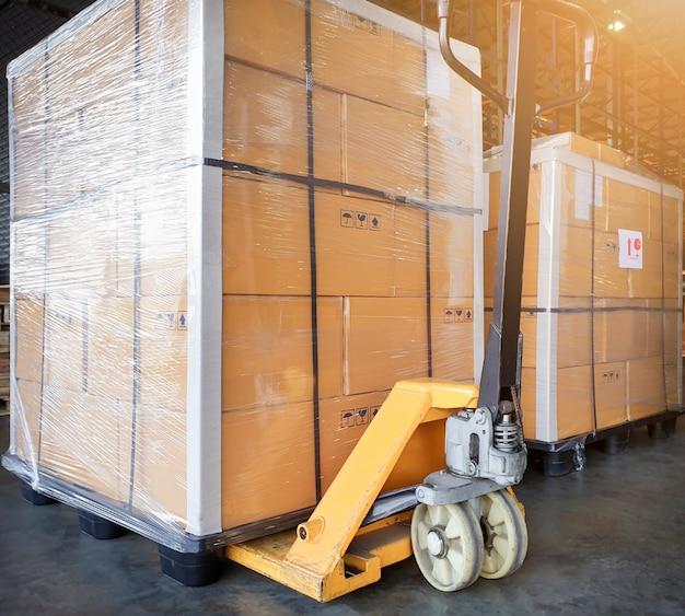 Grote zending palletgoederen en gele handpallettruck. cargo export & shipping magazijn, Premium Foto