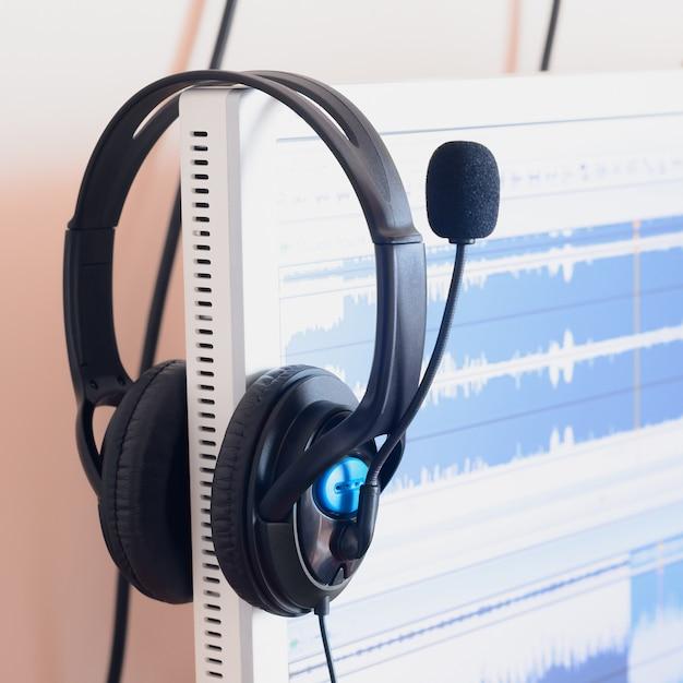 Grote zwarte koptelefoons liggen op het houten bureaublad van de sound designer Premium Foto
