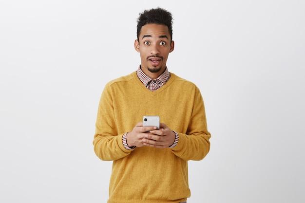 Guy ontving een ongelooflijk bericht. knap verrast amerikaanse man met krullend kapsel met smartphone Gratis Foto