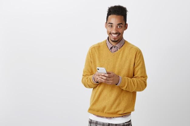 Guy wil bellen. binnen schot van tevreden knappe afro-amerikaanse mannelijk model met afro kapsel in gele trui, smartphone vasthouden, breed glimlachend terwijl berichten met vriend Gratis Foto