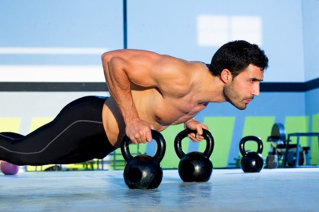 Gym man push-up sterkte push-up met kettlebell Premium Foto