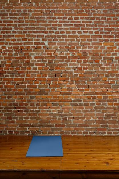 Gymnastiekmat op houten podium met bakstenen muur op achtergrond Premium Foto