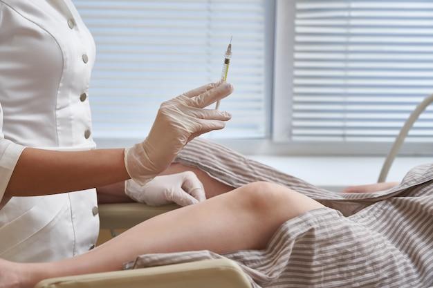 Gynaecoloog met spuit maakt een injectie aan de patiënt in de gynaecologiestoel Premium Foto
