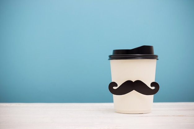 Haal koffiekop met hipstersnor weg op houten lijst over blauwe achtergrond Premium Foto