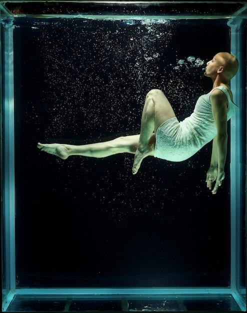 Haarloze vrouw onder water Gratis Foto