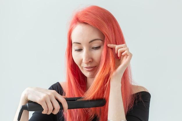 Haarstijl, kapper en mensenconcept - modieuze roodharige vrouw met krultang op witte muur. Premium Foto
