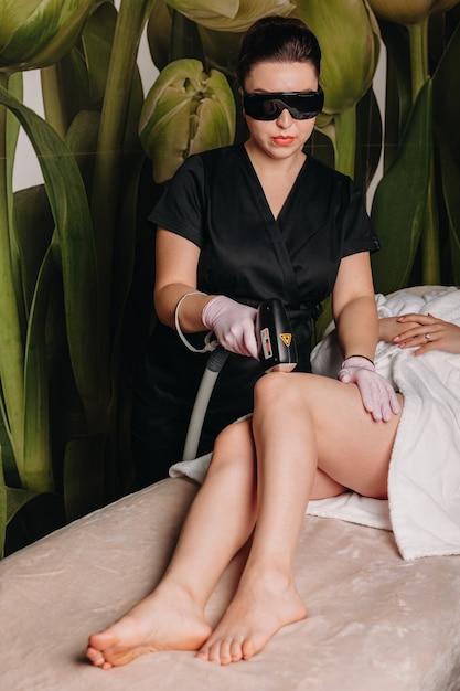 Haarverwijderingsprocedure met laser uitgevoerd in een dermatologiekliniek op de benen van de vrouw Premium Foto