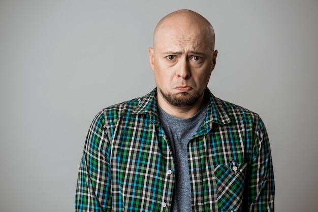 Haatdragend triest emotionele man in overhemd poseren over beige muur Gratis Foto