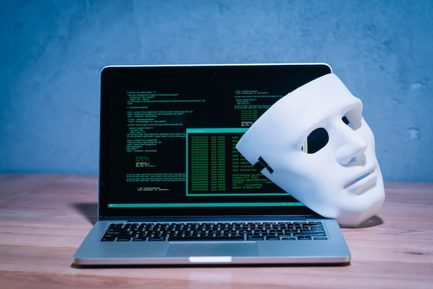 Hackersmasker en laptop Gratis Foto