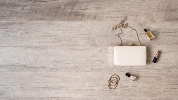 Hairbands; parfum flesje; lippenstift en nagellak met witte koppeling op houten gestructureerde achtergrond Gratis Foto