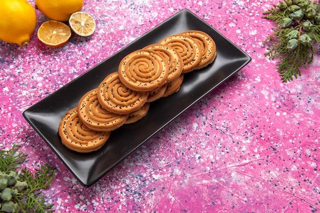 Half-bovenaanzicht zoete koekjes heerlijke kleine koekjes in zwarte vorm met citroenen op lichtroze bureau. Gratis Foto