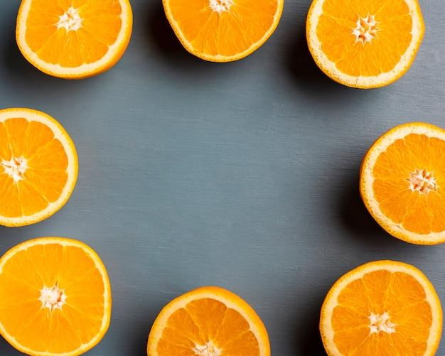 Half gesneden sinaasappelen die frame op lijst vormen Gratis Foto