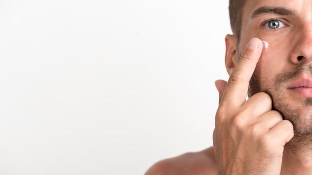 Half gezicht van de shirtless jonge mens die room op zijn gezicht toepast tegen witte achtergrond Gratis Foto
