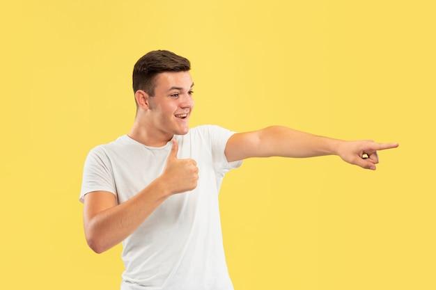 Half-length portret van een blanke jonge man op gele studio Gratis Foto