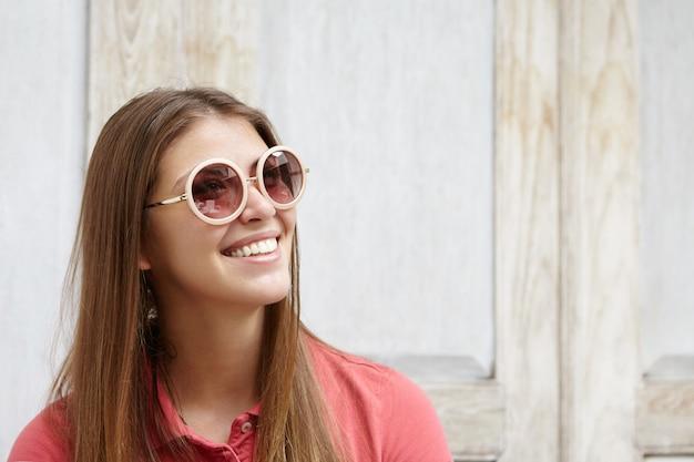 Half profiel van aantrekkelijke modieuze vrouw in ronde tinten glimlachend gelukkig haar witte tanden tonen, verheugend op positief nieuws. Gratis Foto